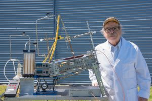 Nazim Muradov standing next to a solar concentrator
